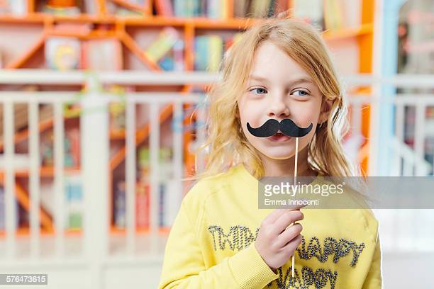 cute girl holding stick with black moustaches