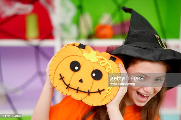 cute girl holding up the pumpkin standing in the halloween party - ugly pumpkins stock photos and pictures
