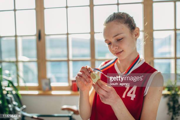 Cute girl in basketball jersey holding a gold medal