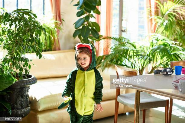 cute girl in dinosaur costume looking at plants - misbehaviour stock pictures, royalty-free photos & images