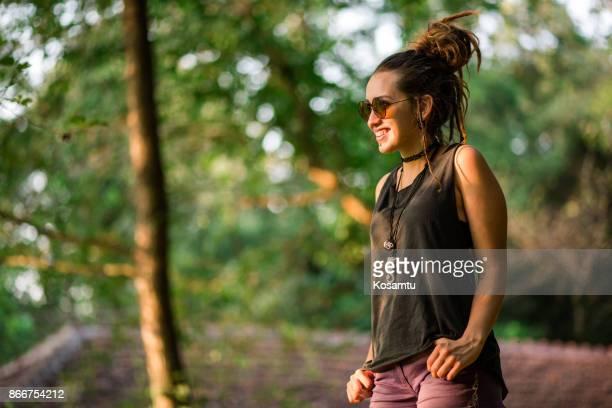 Cute Girl in Dreadlocks Walking In Nature