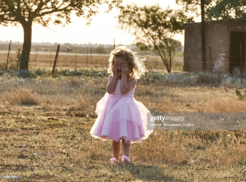 Cute Girl In Dress Covering Face With Hands While Standing On Grassy Field : Stock Photo