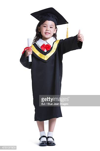 Cute girl in graduation gown doing thumbs up