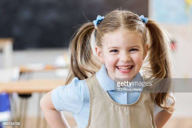 Linda chica en su salón de clase preescolar