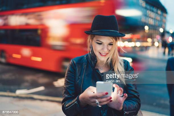 Cute girl in London using smartphone