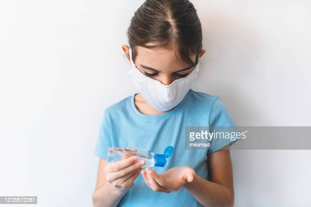 cute girl in medical mask washing hands by alcohol sanitizers from bottle. coronavirus epidemic - hand sanitizer stock pictures, royalty-free photos & images