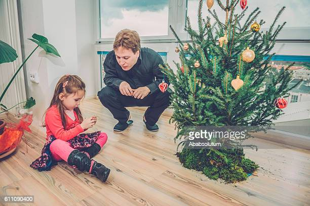 Cute Girl in Pink and Father Decorating Christmas Tree, Europe