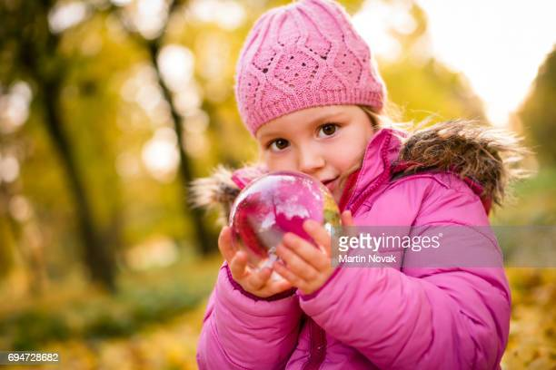 Cute girl in pink jacket holding crystal ball