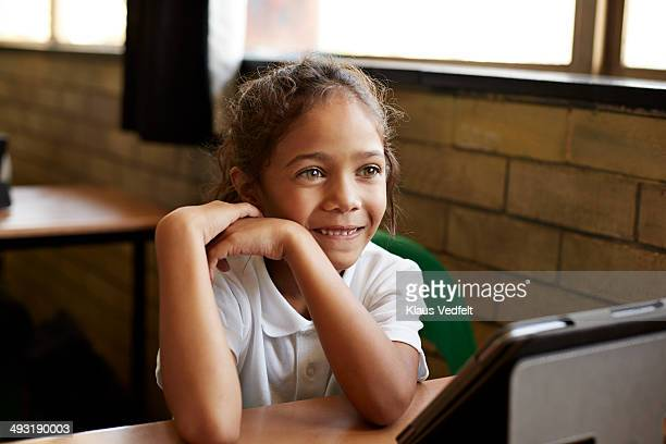 Cute girl in schoolclass with tablet in front