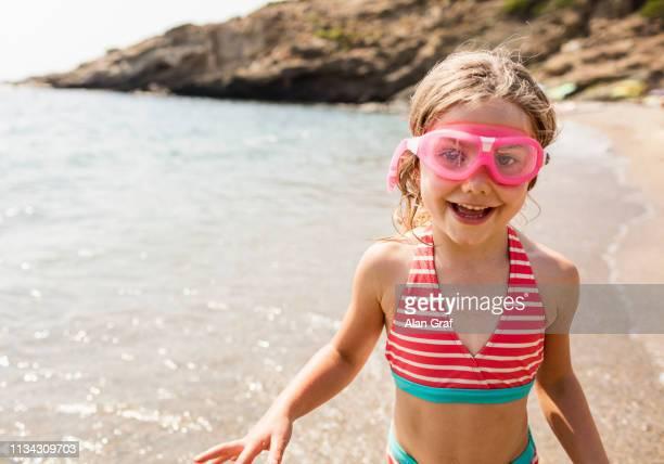 Cute girl in swimming goggles on beach, Portoferraio, Tuscany, Italy
