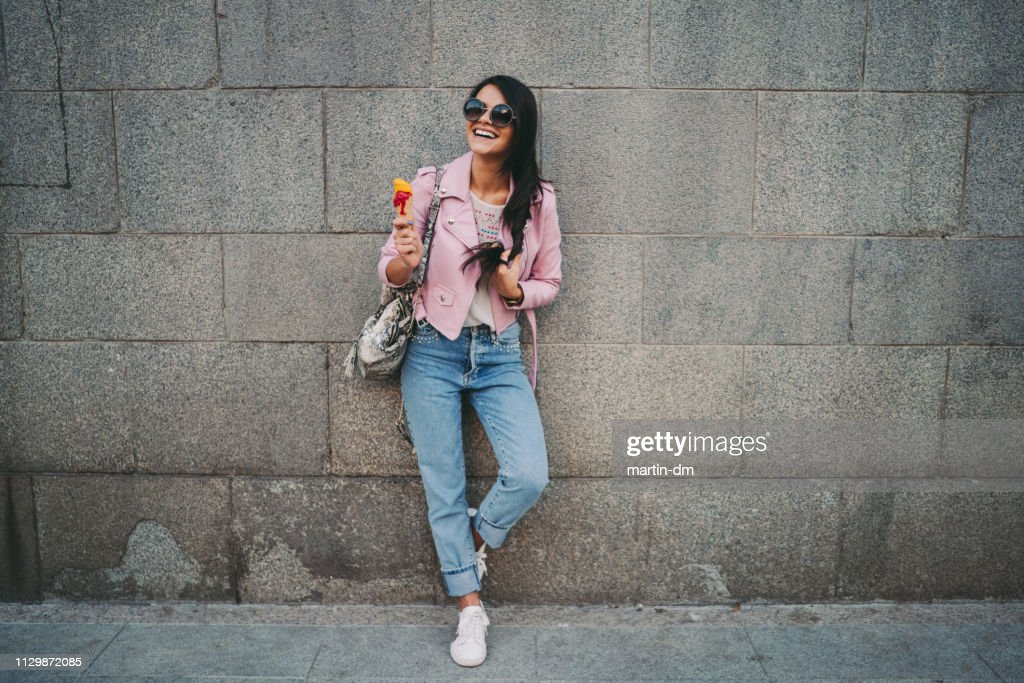 Cute girl in the city eating ice-cream : Stock Photo
