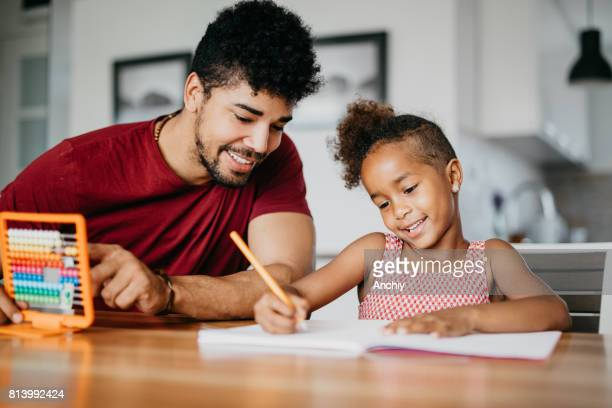 cute girl is doing math with a help of her dad - homeschool stock photos and pictures