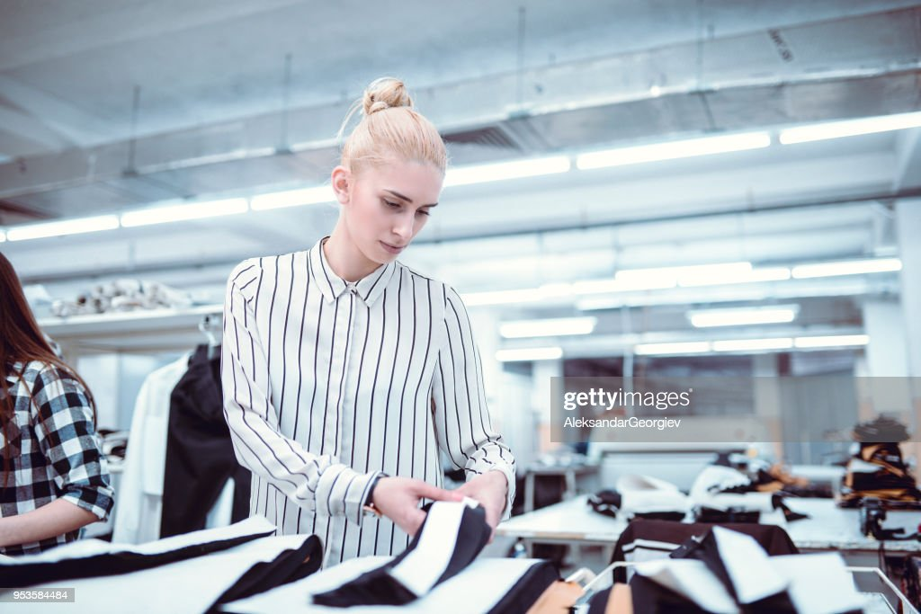 Cute Girl is Measuring Clothes at Work : Stock Photo