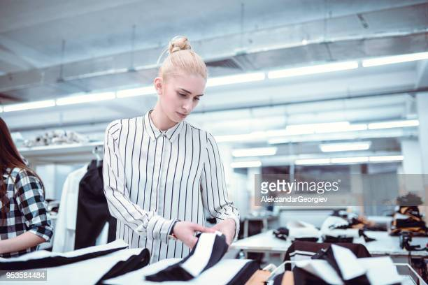 Cute Girl is Measuring Clothes at Work