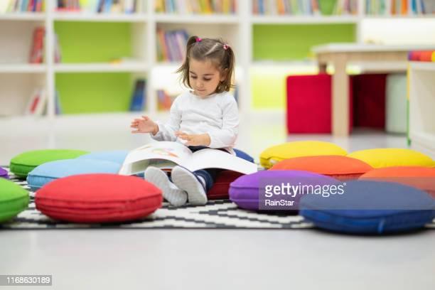 ragazza carina sta leggendo un libro seduto nella biblioteca del vivaio - educazione di scuola materna foto e immagini stock