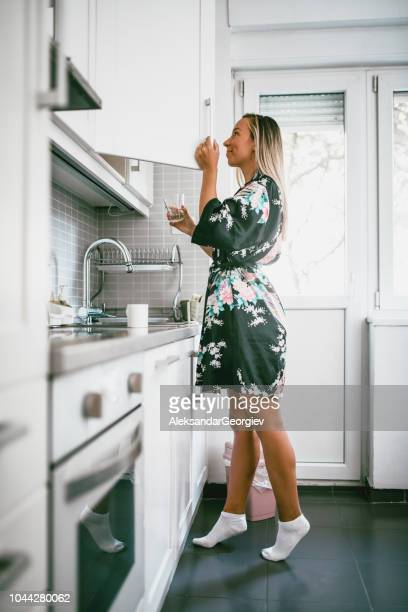 cute girl is searching for a coffee from kitchen pantry - armadietto da cucina foto e immagini stock