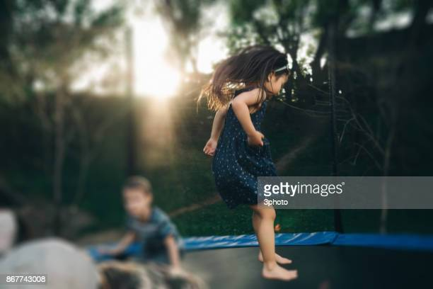 Cute girl jumping on outdoors trampoline