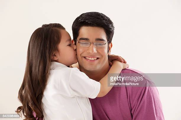 cute girl kissing her father on white background - indian girl kissing stock photos and pictures