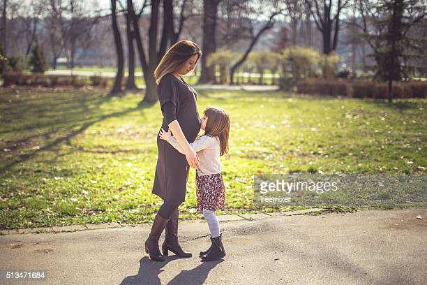 Cute girl kissing her mother's pregnant stomach
