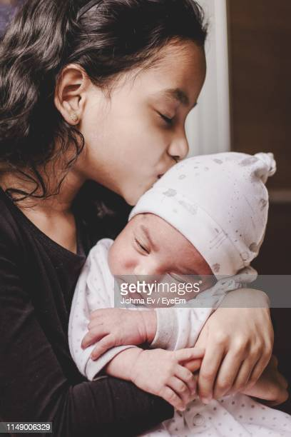 cute girl kissing on brother head at home - arabian girl kissing stock photos and pictures