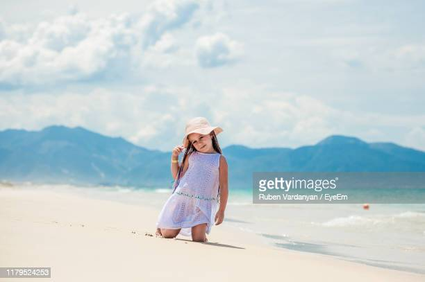 cute girl kneeling on beach against sky - ruben vardanyan stock pictures, royalty-free photos & images