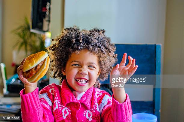 Cute girl laughing and holding up hamburger in kitchen