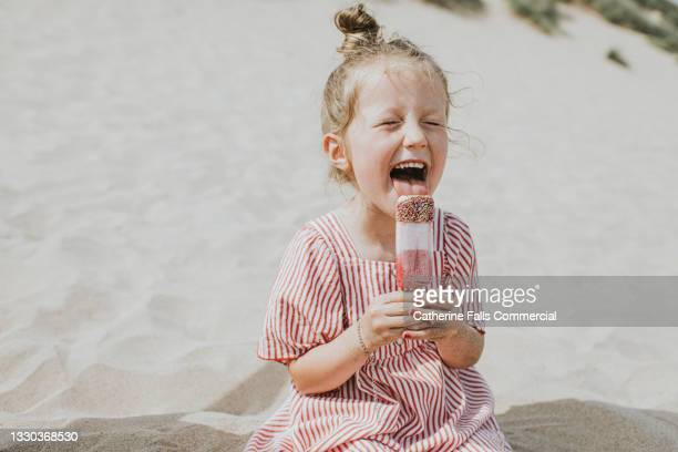 cute girl licks a ice lolly, while sitting on the beach - childhood stock pictures, royalty-free photos & images