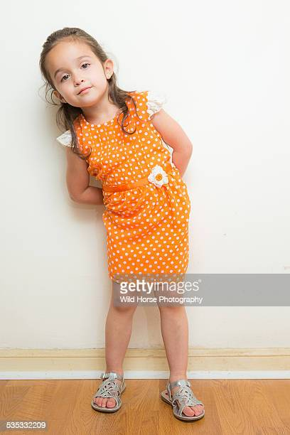cute girl looking at camera in orange dress - orange dress stock pictures, royalty-free photos & images