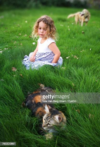 Cute Girl Looking At Cat Lying On Grass At Park