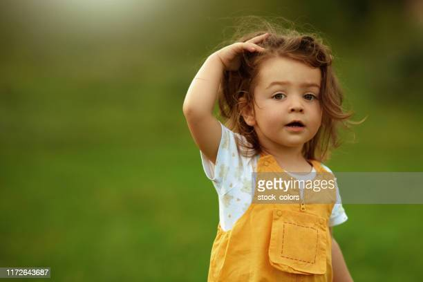 cute girl looking at the camera - yellow dress stock pictures, royalty-free photos & images