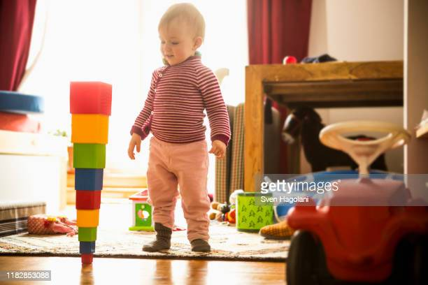 cute girl looking at toy in living room - arrangement stock pictures, royalty-free photos & images