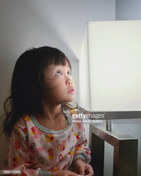 cute girl looking away while sitting at home - central kalimantan stock pictures, royalty-free photos & images