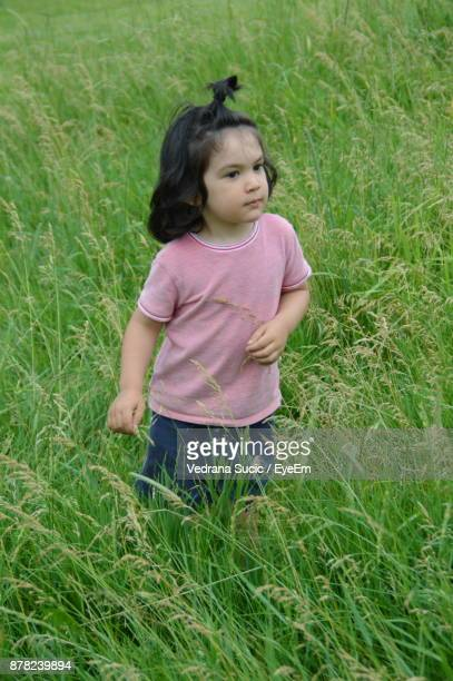 Cute Girl Looking Away While Standing On Grassy Field