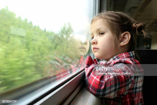 cute girl looking through window of train - train interior stock photos and pictures