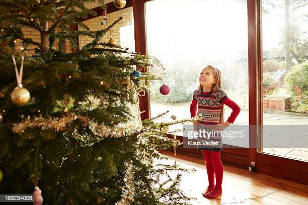 Cute girl looking up at decorated christmas tree