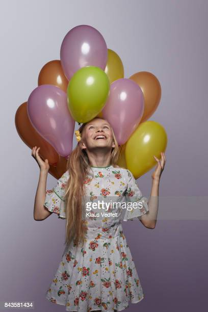 Cute girl looking up at stack of balloons