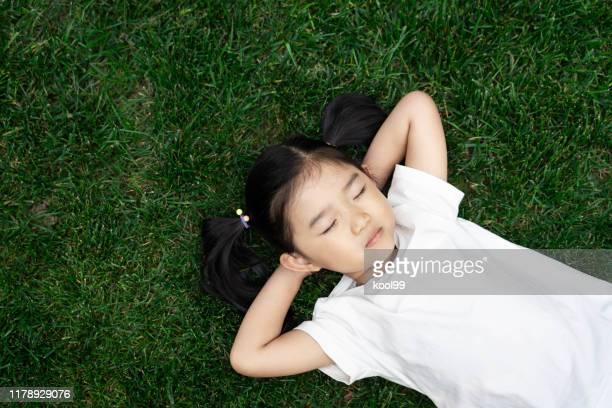 nettes mädchen auf dem rasen liegend - lying down stock-fotos und bilder
