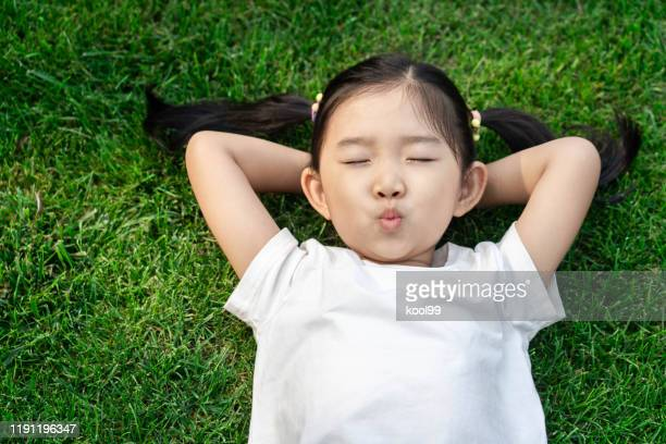 cute girl lying down on the lawn - tranquil scene stock pictures, royalty-free photos & images