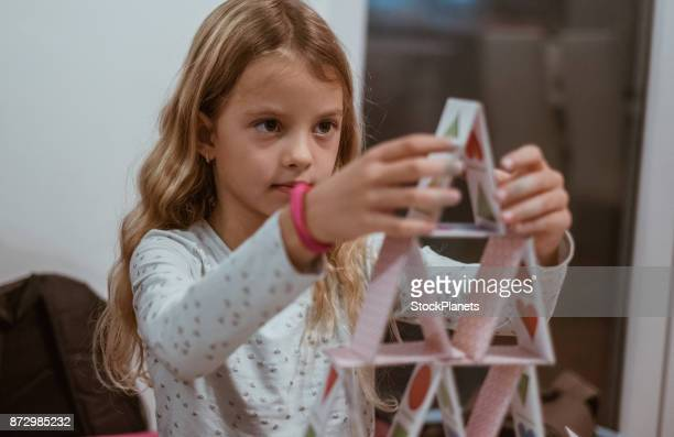 Cute girl making house of cards
