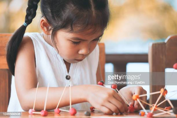 cute girl making molecule model on wooden table in porch - concentration stock pictures, royalty-free photos & images
