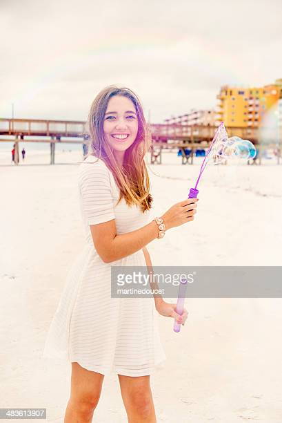 Cute girl making soap bubbles on the beach with rainbow.