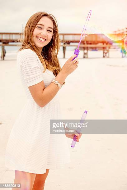 """cute girl making soap bubbles on the beach with rainbow. - """"martine doucet"""" or martinedoucet stockfoto's en -beelden"""