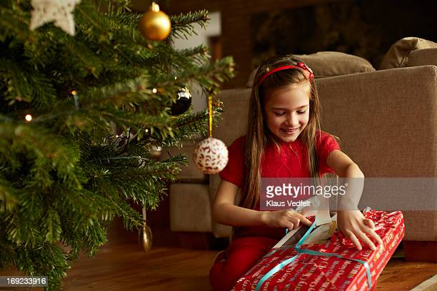 Cute girl opening christmas present