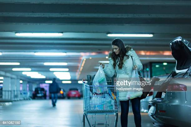 Cute girl, packing things from supermarket in car trunk