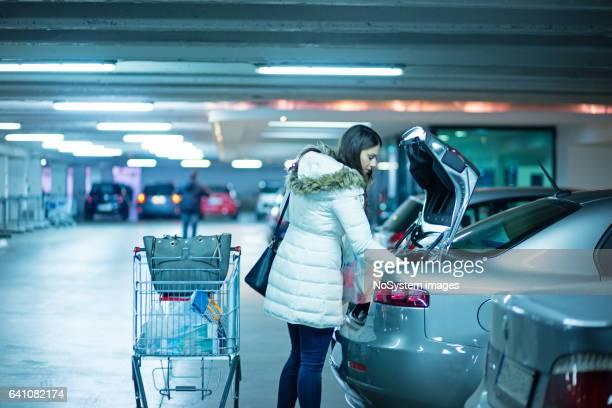 Niedliche Mädchen packt Sachen vom Supermarkt im Kofferraum eines Autos