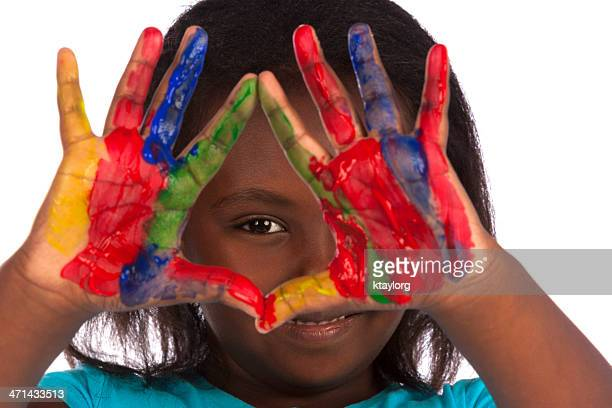 cute girl peeks through painted hands - finger painting stock pictures, royalty-free photos & images