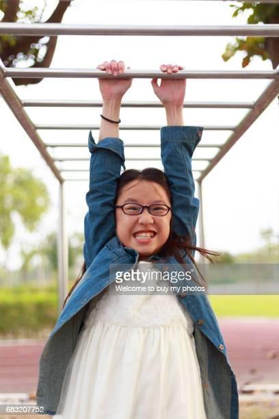 Cute girl playing horizontal bar at the elementary schoolyard.