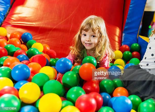 Cute girl playing in the ball pool.