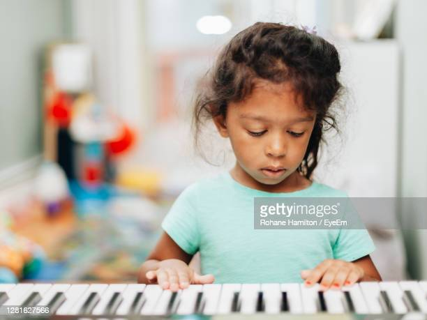 cute girl playing piano at home - hamiltonmusical stockfoto's en -beelden