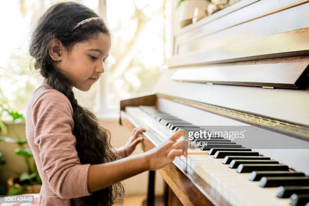 Cute girl playing piano at home